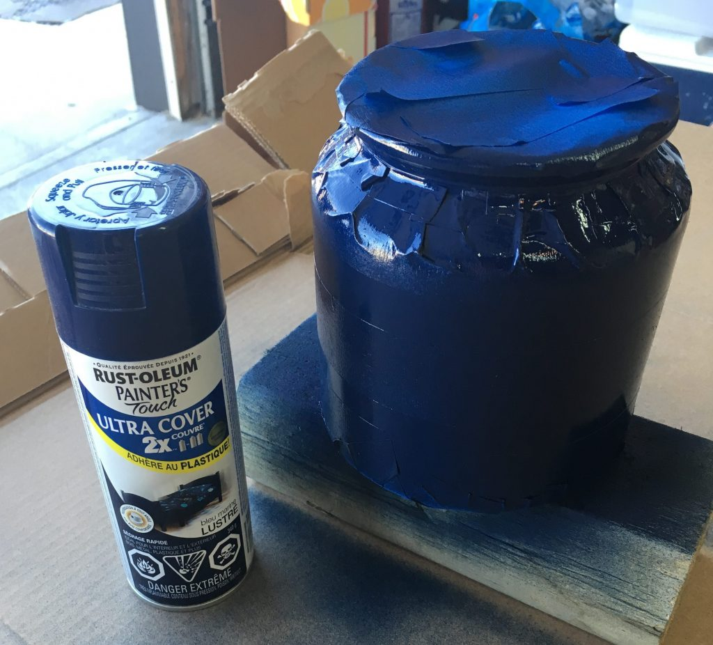 In a well-ventilated area, spray the entire jar with quick strokes, coating evenly.  Allow paint to dry before peeling tape (as shown below).