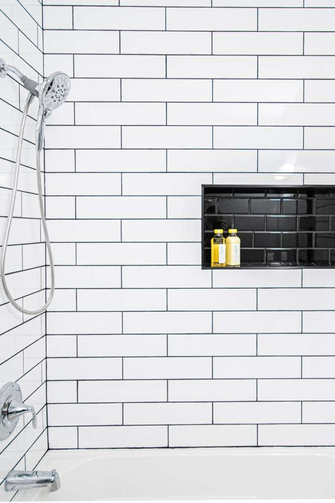 bathroom shower with white and black tile