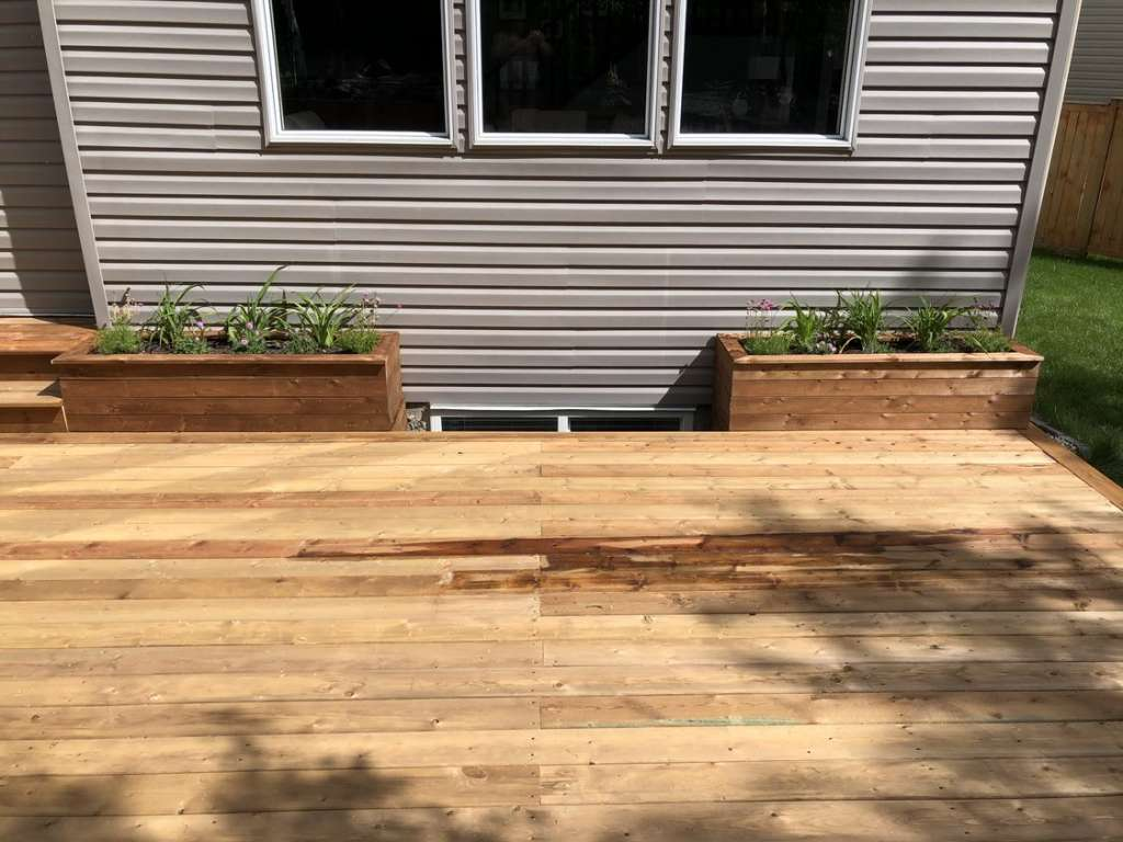 wooden planter boxes with plants growing from it